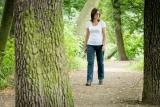 Jana jde vzrostlou alejí stromů