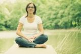 Jana sedí na mole u rybníka v tureckém sedu spokojená