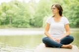 Jana sedí na mole u rybníka v tureckém sedu a dívá se do strany